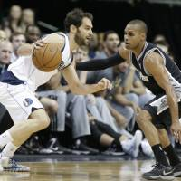 Texas tussle: Dallas' Jose Calderon drives against San Antonio's Patty Mills in the first half on Thursday night. The Spurs downed the Mavericks 109-100. | AP