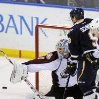 Let nothing through: Avalanche goalie Semyon Varlamov (left) makes a save as teammate Nathan MacKinnon (29) defends against the Blues' Jaden Schwartz during Saturday's game. | AP