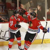 Bring it in: The Blackhawks' Patrick Sharp (left) celebrates his goal with teammate Jeremy Morin on Sunday in Chicago. | AP