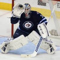 High catch: Winnipeg's Michael Hutchinson makes a save during the first period against Minnesota on Monday night. | AP