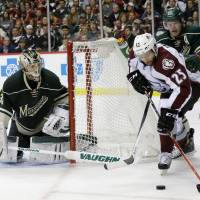 Well covered: Minnesota's Darcy Kuemper (left) and Ryan Suter defend Colorado's Maxime Talbot in Game 4 on Thursday. | AP