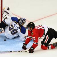 Sneak attack: The Blackhawks' Patrick Sharp scores past Blues goalie Ryan Miller during Game 6 of their playoff series on Thursday in St. Louis. Chicago clinched the series with a 5-1 win. | AP