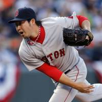 One scoreless frame: Boston's Junichi Tazawa fires a pitch against Baltimore in the eighth inning on Monday in their season opener. The Orioles downed the Red Sox 2-1. | AP