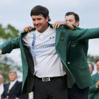 Triumph: New Masters champion Bubba Watson is helped into his green jacket by 2013 champion Adam Scott on Sunday in Augusta, Georgia. Watson won the Masters for the second time in three years. | REUTERS