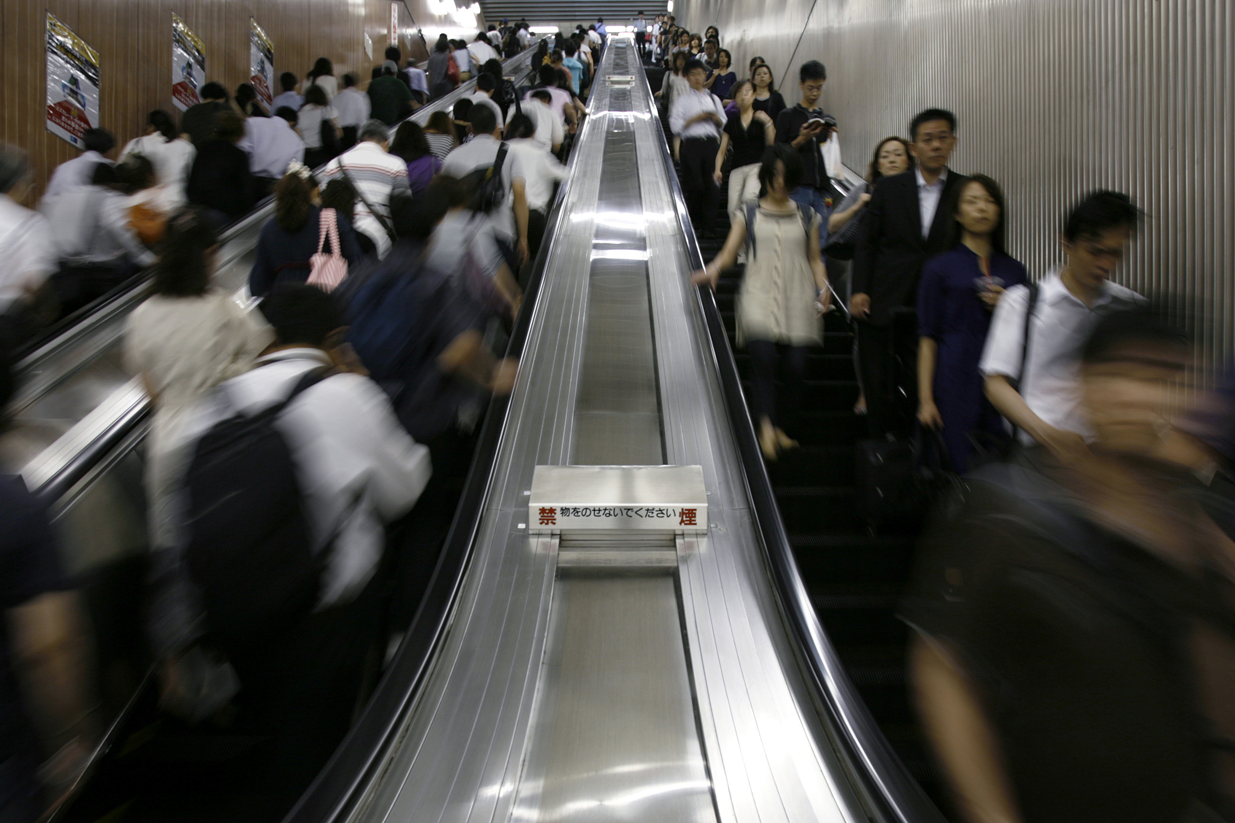 Going down: Commuters use escalators at Tokyo Station in August 2009. | REUTERS