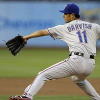 Knocked out: Texas starter Yu Darvish fires a pitch against Oakland in the first inning on Monday night. | AP