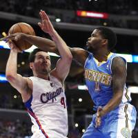 Winning feeling: Los Angeles' J.J. Redick (left) tries to shoot as Denver's Aaron Brooks defends during the Clippers' 117-105 win on Tuesday. | AP