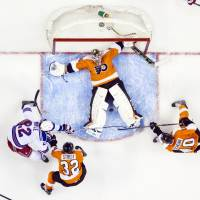 Flat out: Philadelphia goalie Steve Mason stops the puck between his legs during the Flyers' 5-2 win on Tuesday. | AP