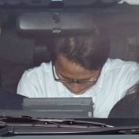Katsuya Takahashi is transported by police after his 2012 arrest. | KYODO