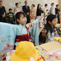 First-graders wearing kimono take a seat before an entrance ceremony held Tuesday at Ryori Elementary School in Ofunato, Iwate Prefecture. | KYODO