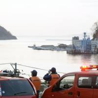 Firefighters on high ground in Onagawa, Miyagi Prefecture, monitor the sea early Thursday for tsunami from an earthquake off Chile. The area took severe damage from the massive tsunami spawned on March 11, 2011. | KYODO