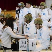 Ground Self-Defense Force personnel undergo health checkups before they are dispatched to cull birds stricken with a strain of the avian flu virus at a chicken farm in Taragi, Kumamoto Prefecture, on Monday. | KYODO