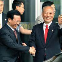 Tokyo Gov. Yoichi Masuzoe (right) shakes hands with an official from Beijing as he arrives in the city on Thursday. | KYODO
