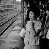 A work by award-winning photographer Shisei Kuwabara shows a woman waiting for a train at Minamata Station in Kumamoto Prefecture in August 1960 after leaving her son afflicted with Minamata disease behind.   SHISEI KUWABARA/KYODO