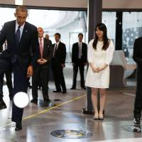 U.S. President Barack Obama stops a soccer ball kicked by Honda Motor Co.'s Asimo robot during a visit to the National Museum of Emerging Science and Innovation in Tokyo on Thursday. | REUTERS