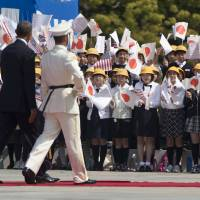 U.S. President Barack Obama walks past flag-waving children to inspect Japanese troops upon arriving for the welcoming ceremony at the Imperial Palace in Tokyo on Thursday. Later in the day, he places a prayer tablet at Meiji Shrine in Tokyo.   AP