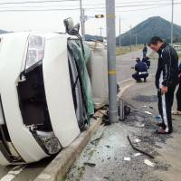 A car involved in a crash with a police car lies on its side on a street in Tanba, Hyogo Prefecture, on Sunday. | KYODO