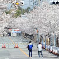Evacuees from Tomioka, near the Fukushima No. 1 plant, make a short trip home April 9. | KYODO