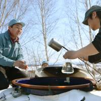 Brewers in the town of Biei, Hokkaido, sample sake Wednesday that was aged under the snow. | KYODO