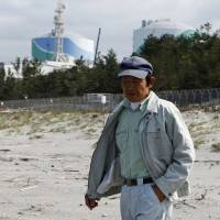 Yukio Nakano, 55, a nearby resident and conservationist, walks along the beach next to the Kyushu Electric Power Co.'s Sendai nuclear power plant in Satsumasendai, Kagoshima Prefecture, on April 5. | REUTERS