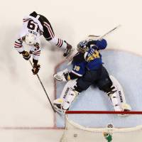 Go sing the blues: The Blackhawks' Jonathan Toews scores the winner past Blues goalie Ryan Miller during Game 5 on Friday in St. Louis.   AP