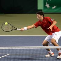 Game over: Japan's Yasutaka Uchiyama hits a return toward the Czech Republic's Radek Stepanek and Lukas Rosol as teammate Tatsuma Ito looks on during their Davis Cup doubles match on Saturday. | AFP-JIJI