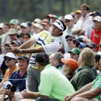 Man of the people: Bubba Watson hits from the gallery during the second round of the Masters on Friday in Augusta, Georgia. | AP