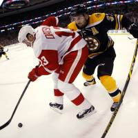 Fly on by: The Red Wings' Pavel Datsyuk (left) tries to keep the puck away from Bruins center Patrice Bergeron on Friday night in Boston. | AP
