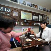 A patron (left) clinks glasses with a female friend at rail-themed pub Tetsudo-Izakaya Little TGV in Tokyo's Akihabara district on March 14. | YOSHIAKI MIURA