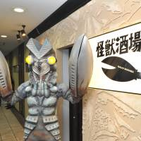 Alien Baltan, proprietor of Kaiju Sakaba, a restaurant-bar in Kawasaki, stands at the entrance on March 13 ahead of its official opening. According to the management, Alien Baltan 'hides himself from human beings' during business hours. | YOSHIAKI MIURA