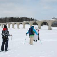 Tourists walk through snow to see the 'phantom bridge,' which is only visible for a few months a year as the lake's water level rises and falls, on March 14. | RYOJI IWASAKI/KYODO