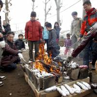 Fathers and their children roast sweet potatoes on a campfire in Niiza, Saitama Prefecture, in February. | KYODO