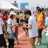 Runners exchange business cards after a separate ekiden held for corporate participants in Tokyo. | KYODO