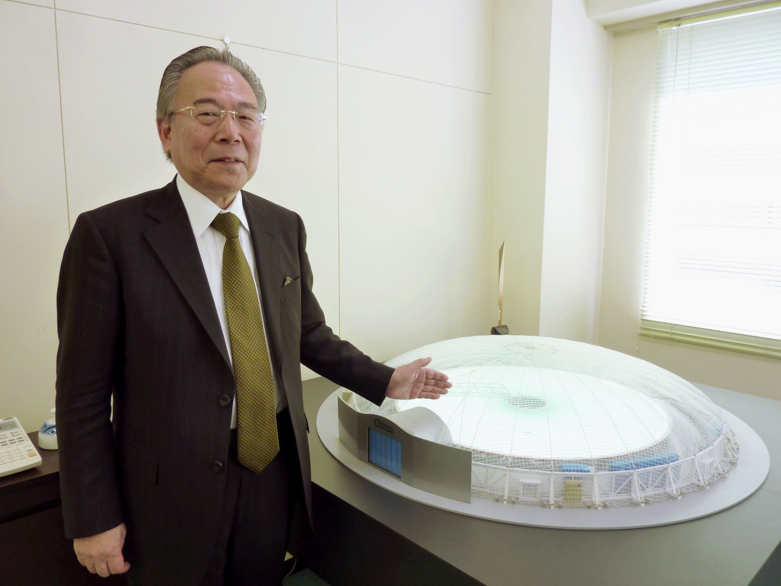 Takaaki Abe, founder of indoor farming firm Granpa, points to a model of one of his facilities in Yokohama in March. | KYODO