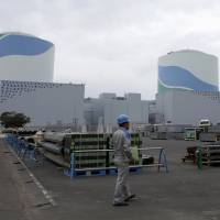 An employee of Kyushu Electric Power Co. walks in front of reactor buildings at the company's Sendai nuclear power plant in Satsumasendai, Kagoshima Prefecture, on April 3. | REUTERS