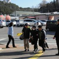 Children walk to Furumichi Elementary School, which reopened on April 7 in the Miyakoji district in the city of Tamura, Fukushima Prefecture. The shopping facility, which opened the day before, is seen in the background. | FUKUSHIMA MINPO