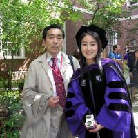 Kanae Doi is pictured with her father at her graduation ceremony at New York University School of Law in 2006. | HUMAN RIGHTS WATCH