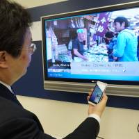 Ryosuke Sumitomo, a research engineer at the User Interface Laboratory at KDDI R&D, talks to his panda avatar assistant to get information about what is being shown on TV. | KAZUAKI NAGATA