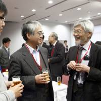 Kyushu University professor Masato Wakayama (right) chats with participants at a symposium on mathematics for industry at the University of Tokyo's Institute of Industrial Science on Feb. 22. | KYODO