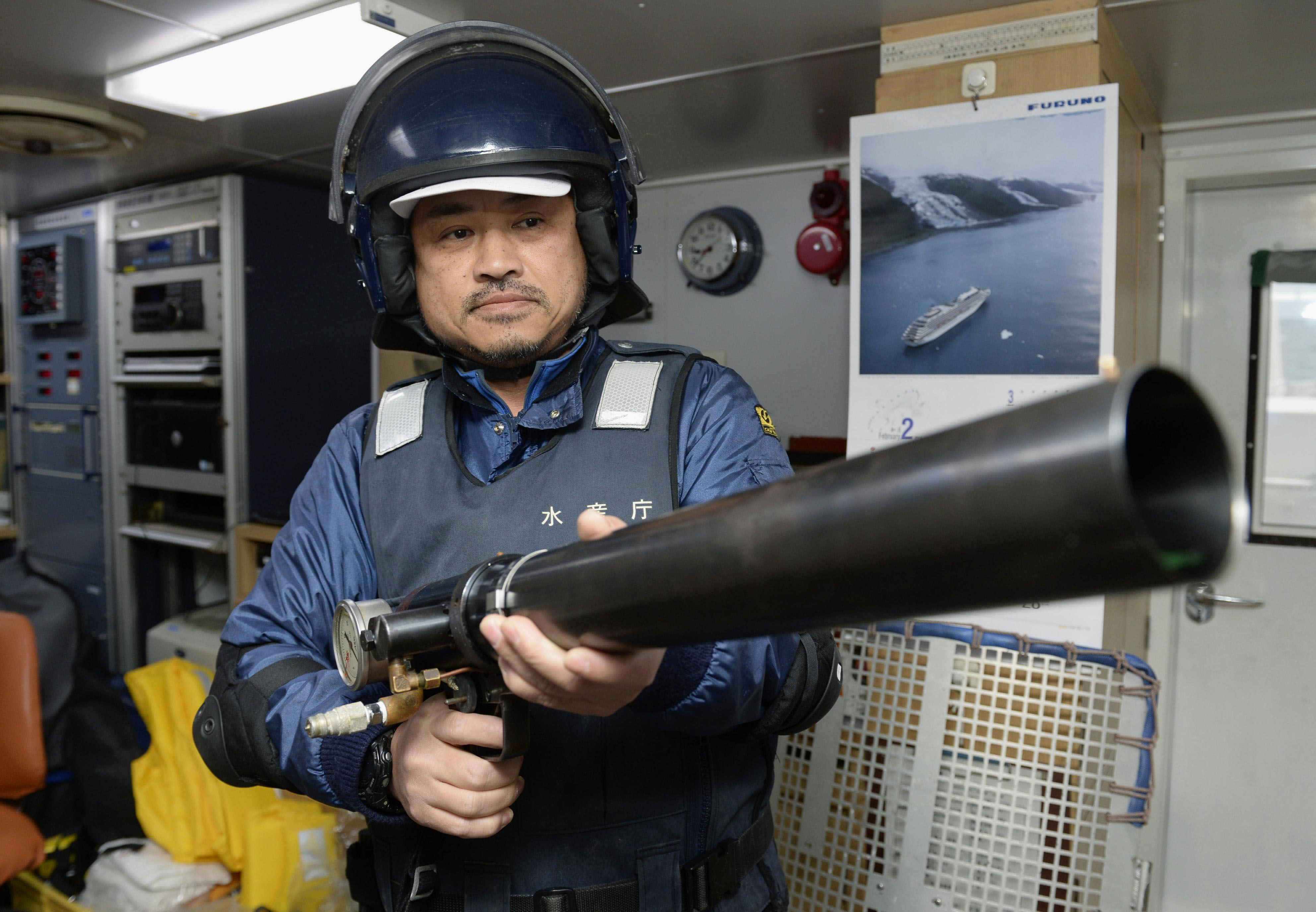 A member of the Fisheries Agency patrol boat Hakuo Maru holds a paint ball gun used to mark ships suspected of illegally fishing in Japanese waters in February while off the coast of Tsushima Island in Nagasaki Prefecture. | KYODO