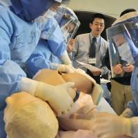 Physician Hironobu Tokunaga (rear, center) teaches medical staff at Ishikawa Prefectural Central Hospital in Kanazawa how to treat people for radiation exposure in a practice session on Feb. 9.   KYODO