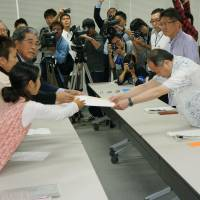 Yonaguni residents submit a letter to Okinawa Defense Bureau chief Hirofumi Takeda (right) requesting the cancellation of a plan for their island to host a Ground Self-Defense Force base, on Monday in Kadena, Okinawa Prefecture. | KYODO