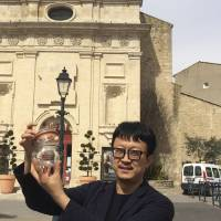 Beijing artist Liang Kegang collects fresh air in Provence, France, on March 29. The jar of air, a piece of conceptual art to protest his native city's choking pollution, has fetched $860 in a small auction. | AP