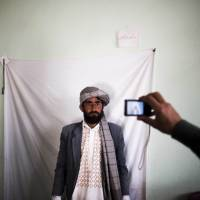 A resident of Herat, in northwestern Afghanistan, has his picture taken Monday in order to receive a voter card for Saturday's presidential election. The poll comes as U.S.-led foreign troops withdraw after 13 years of fighting. | AFP-JIJI