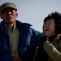 Relatives of victims from the South Korean ferry Sewol disaster stand by the sea in Jindo on Monday. | AFP-JIJI