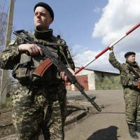 Ukrainian guards stand watch at a base near the Russian border outside the city of Donetsk on Tuesday. | REUTERS