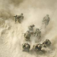 U.S. soldiers protect their faces from rotor wash as wounded comrades are airlifted by a helicopter near Kandahar, Afghanistan, in August 2011. | AFP-JIJI