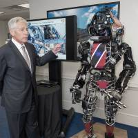 U.S. Defense Secretary Chuck Hagel is briefed on the Atlas robot — one of the most advanced humanoid robots ever built — at the Pentagon on Tuesday. | AFP-JIJI