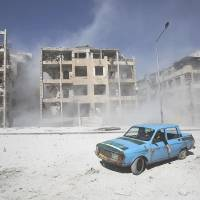 A car is driven through a shattered Aleppo neighborhood on Wednesday. Rebel forces on Thursday accused the regime of again deploying chemical weapons in Damascus. | REUTERS