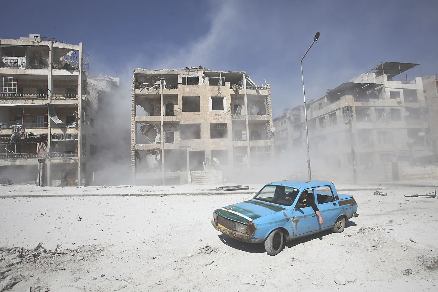 A car is driven through a shattered Aleppo neighborhood on Wednesday. Rebel forces on Thursday accused the regime of again deploying chemical weapons in Damascus.   REUTERS